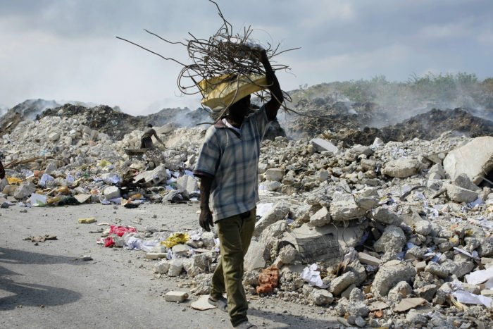A man carries, on his head, a bundle of metal bars salvaged from the rubble of collapsed buildings in Port-au-Prince